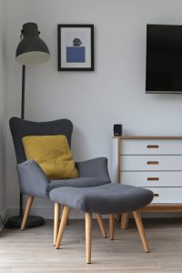 The grey armchair and matching footstool (Homesense) is 'brought to life' with the colourful Beth Jordan Cushion, Jacky Al-Samarraie - Llanbeder Framed Print and the grey Hektar Ikea lamp.