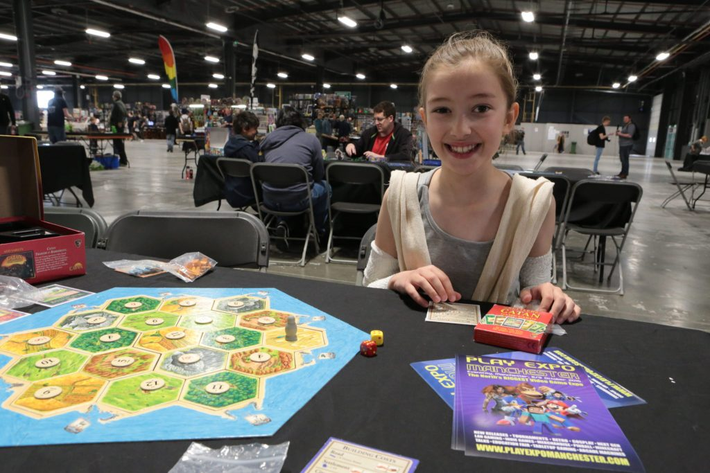 Emily Sitting in front of the board game, 'Settlers of Catan.'