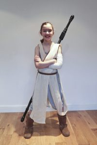 DIY Star Wars Rey costume : Emily in her Rey Costume with her staff strapped to her back and her hair in a Rey hairstyle