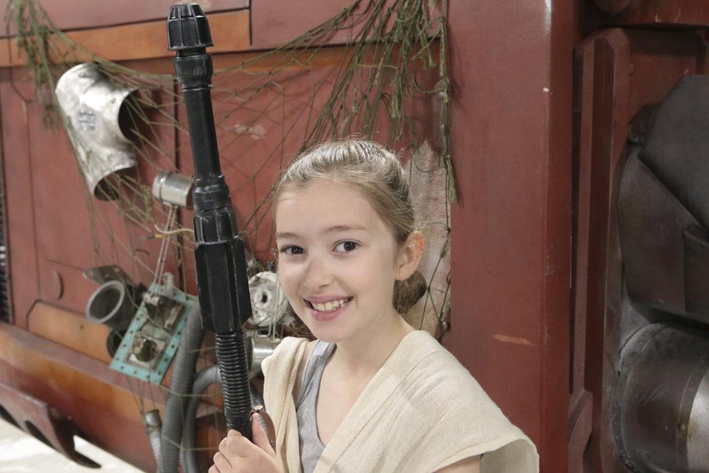 Emily stands in front of Rey's Speeder