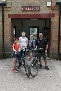 Three of the children in our party pose outside the cycle hire shop with their bikes and one of the staff from the cycle hire shop at Clumber Park National Trust Property