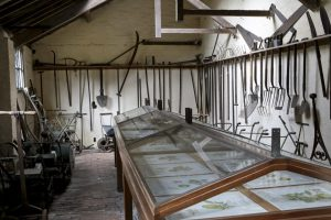 There are plenty of tools lining the walls and machinery such as lawn mowers in this tool shed adjoining the glass house at Clumber Park National Trust Property
