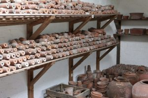 The store rooms adjacent to the glass house are full of shelves filled with clay plant pots of different sizes as Clumber Park National Trust Property