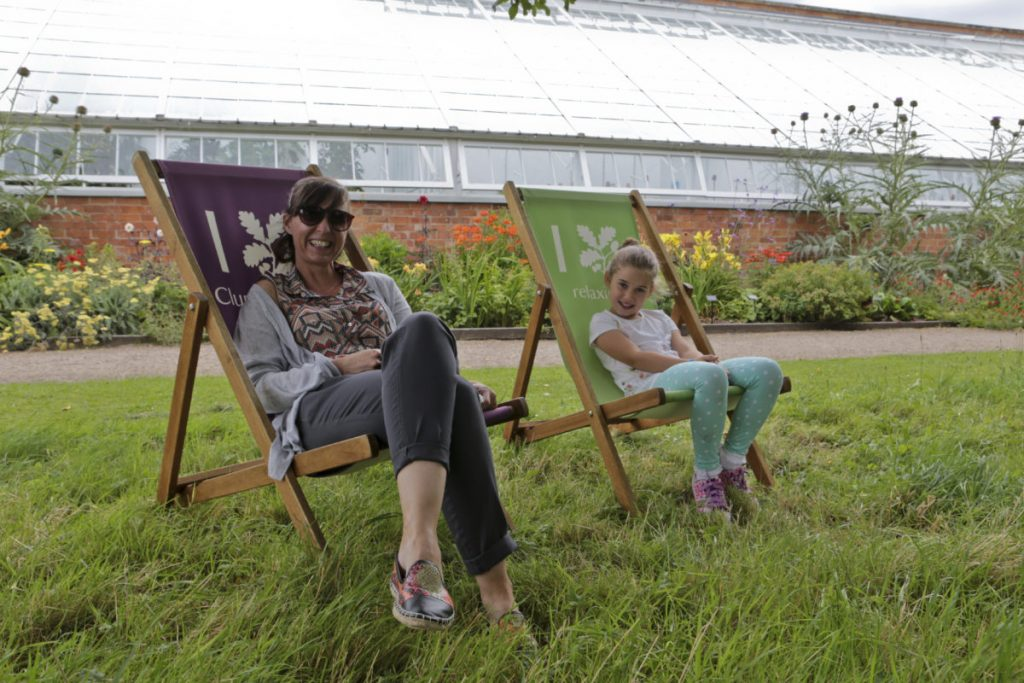 A mother and daughter relax in the National Trust Deck chairs in the orchard in the walled garden at Clumber Park