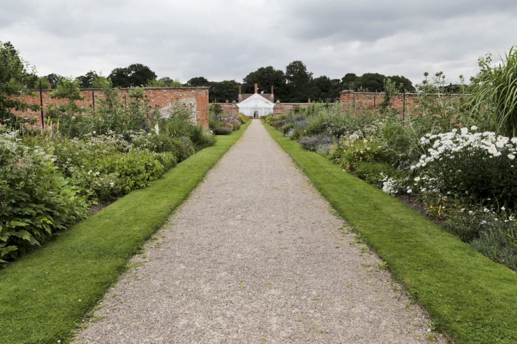 The view from the south gate up to the middle section of the glass house. The gravel path is in the centre of the walled garden and runs from the gate to the glass house past plots of plants, fruits, veg.