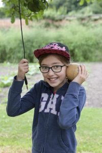 Emily holds a wooden apple to her ear to hear sounds in the apple orchard of the walled garden at Clumber Park National Trust Property