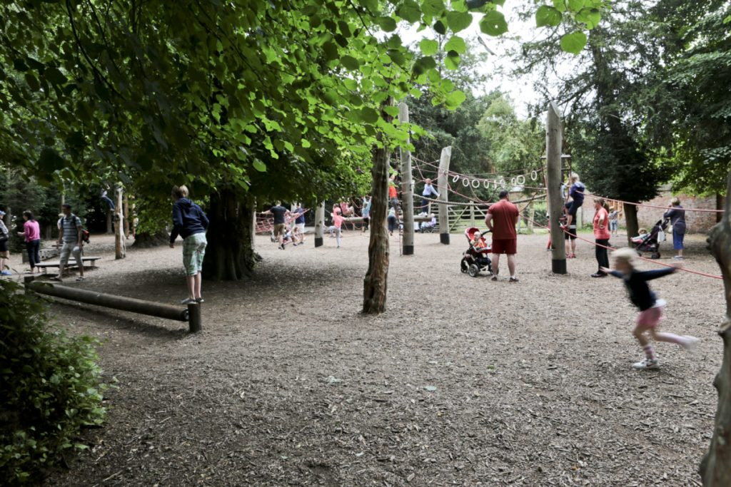 A view of the Adventure Playground at Clumber Park National Trust Property, with children playing. It is through a side gate and leafy and wooded.