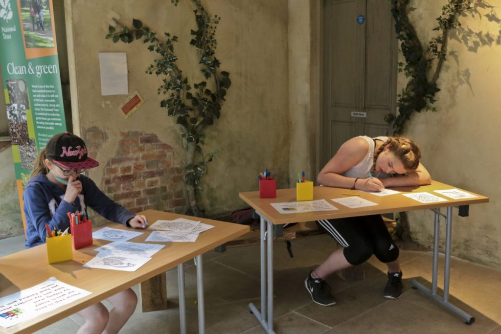 Children sitting at tables and colouring inside the Discovery Centre at Clumber Park National Trust Property