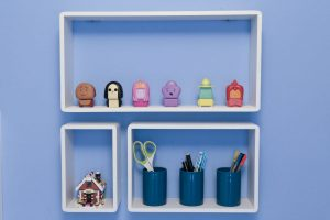 Close up of B & Q White Cube Shelves fitted to blue bderoom wall and filled with Emily's ornaments and pens, pencils and ornaments