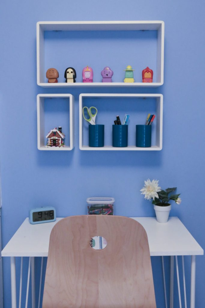 B & Q White Cube Shelves fitted to blue bderoom wall and filled with Emily's ornaments and pens, pencils and ornaments above our DIY children's desk