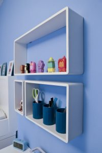 B & Q White Cube Shelves fitted to blue bderoom wall and filled with Emily's ornaments and pens, pencils and ornaments