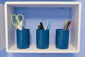 Close up of three blue pencil pots filled with pens, pencils and a pair of scissors on a white B & Q cube shelf