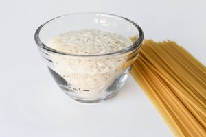 Food portion control. Measuring bowl filled with uncooked rice and dry spaghetti on a table next to it