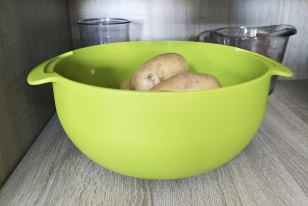 Potatoes in a greed bowl in a cool, dark storage cupboard