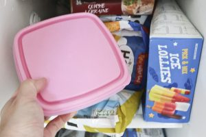 Puting a tupperware container filled with food into the freezer