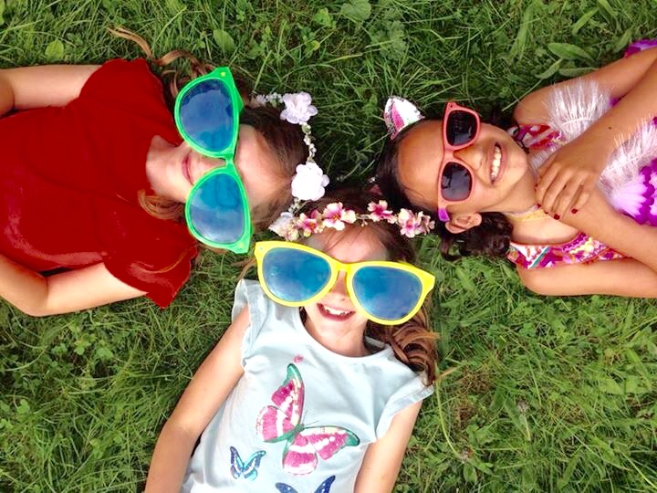 Three girls laying on the grass with giant sunglasses on and smiling
