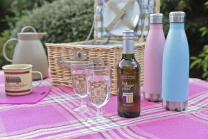 Homesense Al Fresco Dining favourites. A hamper on a picnic blanket with thermos bottles, a coffee thermos, plastic wine glasses, bottle of cordial, enamel mugs.