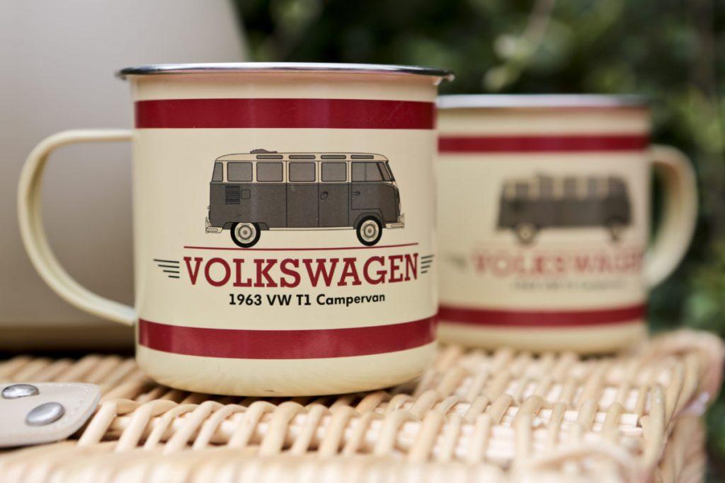 Beige enamel Volkswagen mugs with red stripe motif and campervan image.