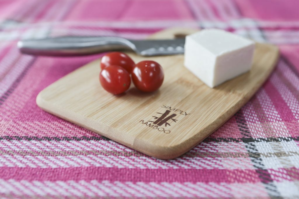 The smallest bamboo chopping board shown with cheese, tomatoes and a knife.