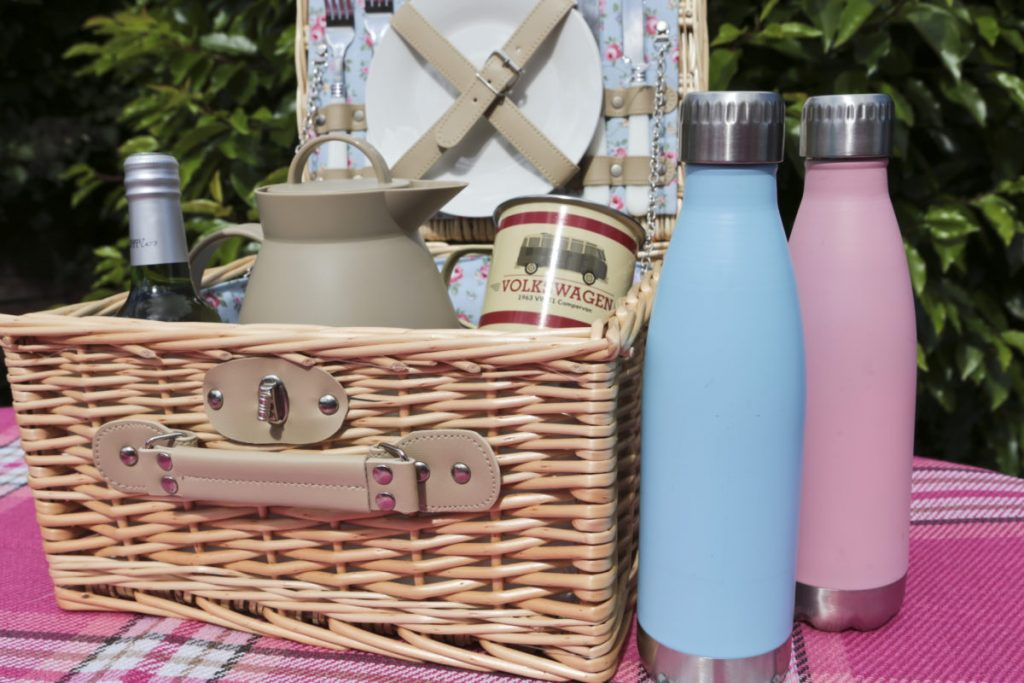 Picnic hamper filled with a thermos and mugs. There are two insulated drinks bottles in pastel pink and blue shades beside the hamper.