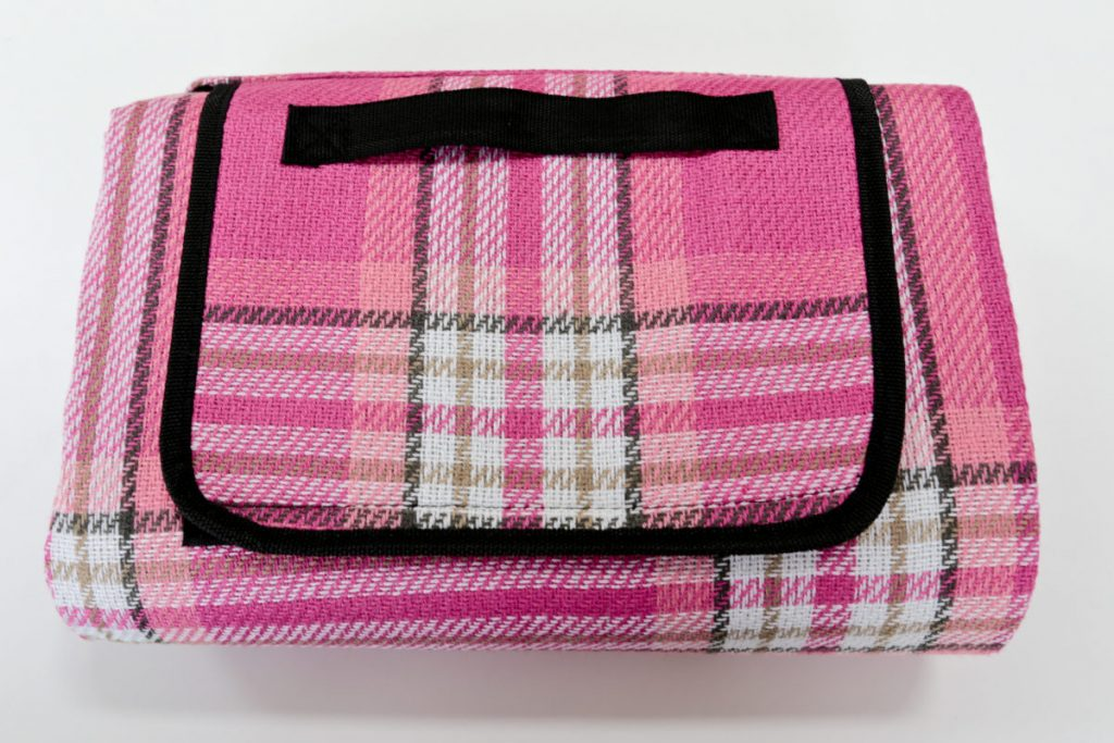 This lightweight, foldable pink tartan picnic blanket with waterproof backing will brighten up any picnic.