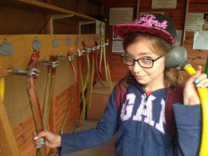 Emily holds an earpiece on the end of a pipe to her ear inside a shed. She's holding a ctick of rhubarb attached by a clamp in her other hand. Sound is conducted through the rhubarb so she can hear it.