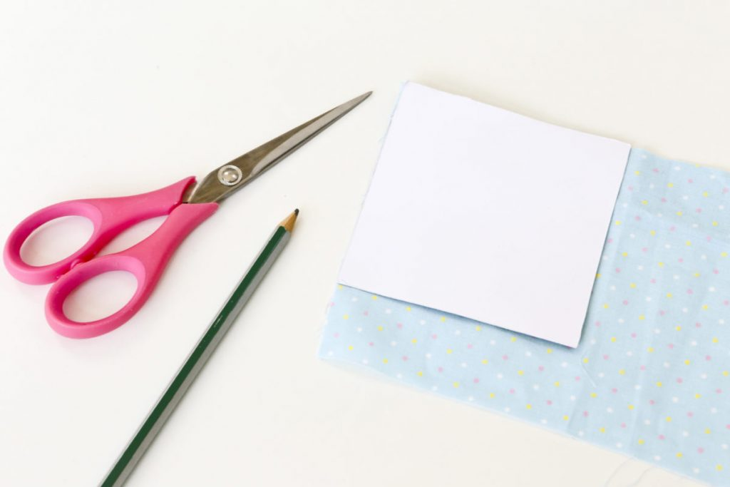The carboard 10x10cm template is placed on the dabric (doubling over the fabric means you only need to cut once to get two squares. with a pair of scissors and pencil beside.