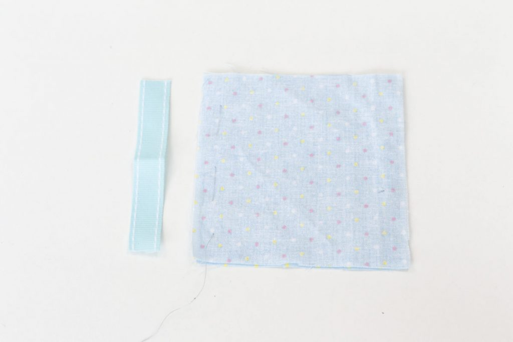 A piece of blue 1cm wide ribbon 10cm long is laid on the table perpendicular to the squares of blue spotted fabric that have been stitched along one seam