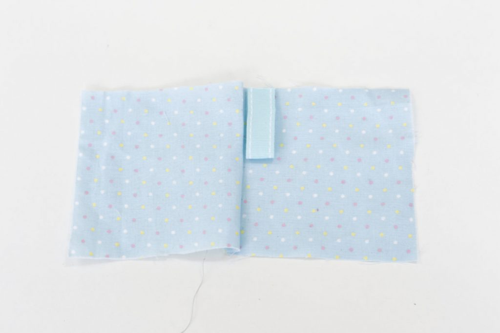After stitching together the two pieces of blue spotted fabric along the first side. The fabric is opened out flat and a piece of 10cm ribbon, folded in half to form a loop is places along the seem with the open edge lined up with the second side of the fabric