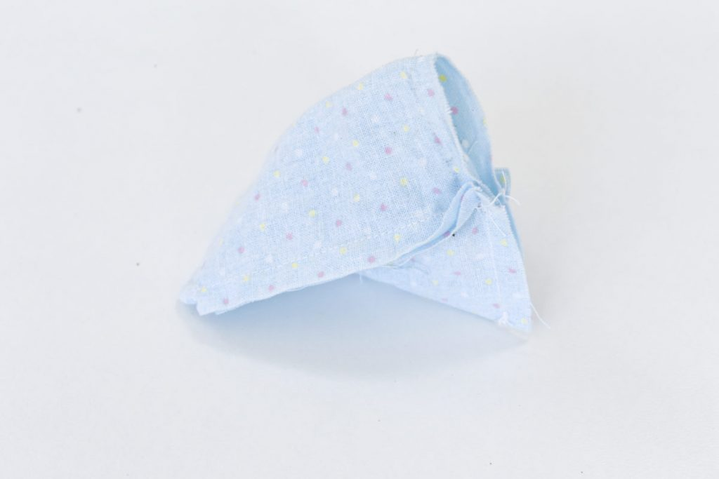 The pyramid lavender bag in blue material with spots has been stitched along the fourth side to the half way point leaving a gap to turn it rightside out and fill with rice/lavender mix