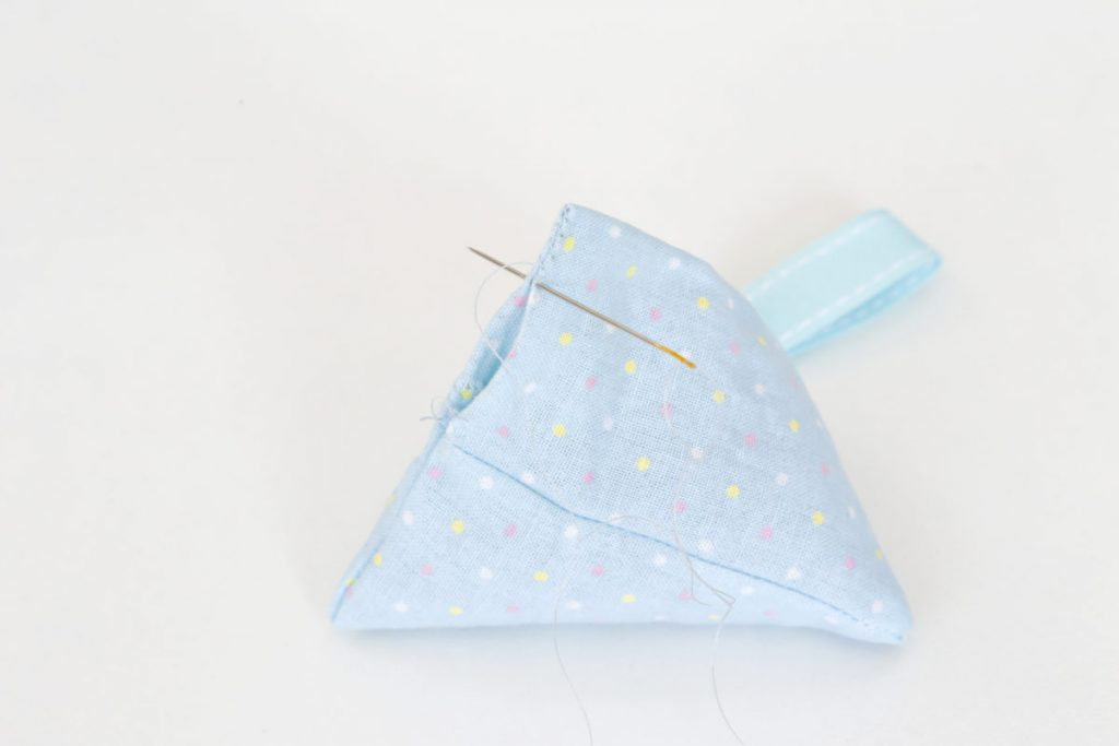 The pyramid lavender bag in blue material with spots is filled and the seam can now be hand stitched closed.