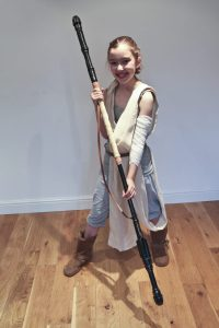 Emily is poised and ready for action as Rey from Star Wars, The Force Awakens. She has the staff, the clothes and the Rey hairstyle.