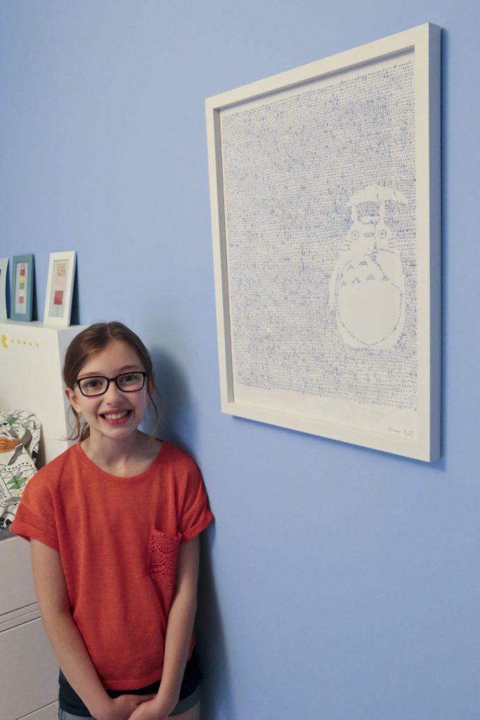 Emily standing beside her framed Totoro print on her blue bedroom wall.