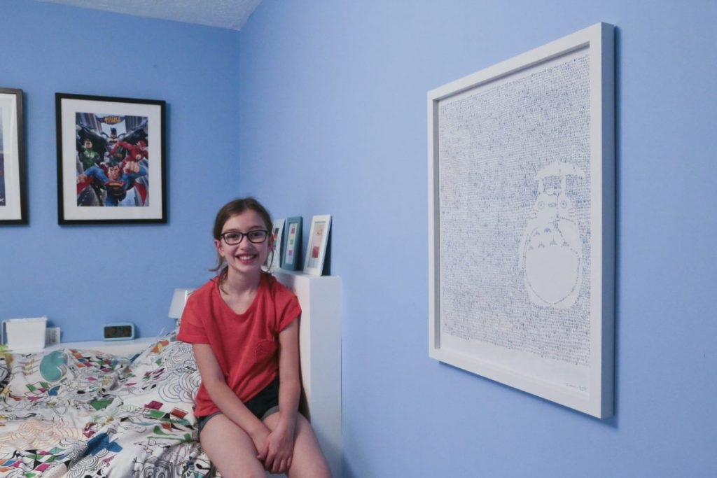 My daughter Emily, sitting on her bed in her bedroom with the signed, framed Mike Matola Totoro print on the wall in the foreground.