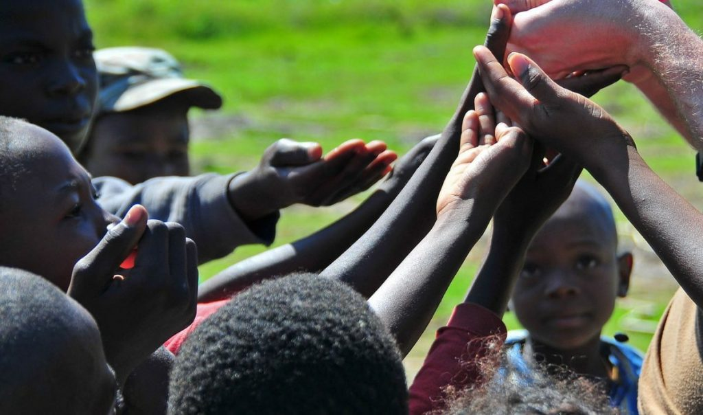 Good news : Children in Haiti reaching up with their hands to get sweets being given out by a relief worker
