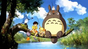 Screen shot from My neighbour Totoro film by Studio Ghibli. It shows Totoro on a tree branch above a lake with other characters from the film
