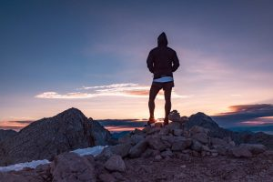 Inspiration. A silhouette of a climber on a summit looking out over a mountain range