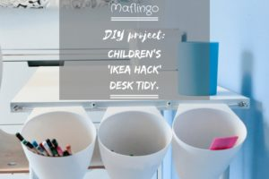 Text overlay DIY project: Children's Ikea Hack Desk Tidy. CLose up of three Bygel containers hanging on a net curtain wire on the end of a children's white desk