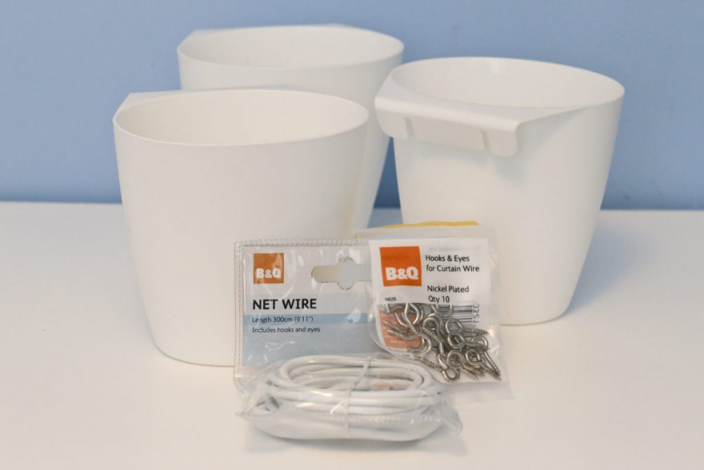 Three Ikea Bygel containers in a cluster on a desk with a packet of B&Q hooks and Eyes and B&Q net curtain wire.