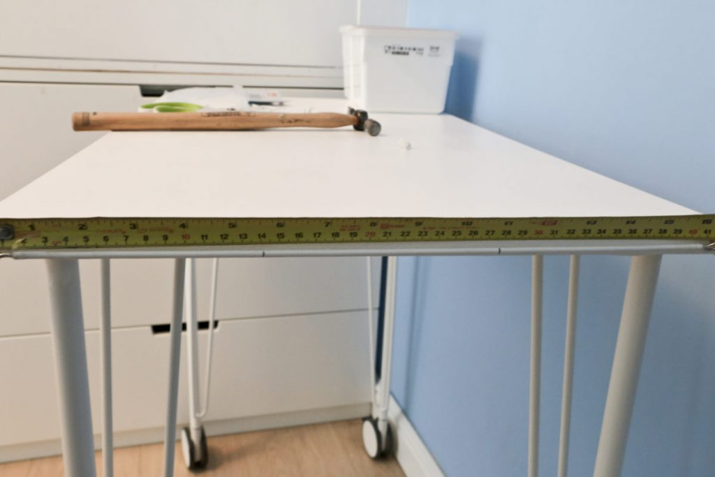 Side view of desk with a metal tape measure above the fixed net curtain wire showing marks at 1/3 and 2/3 of way along wire.