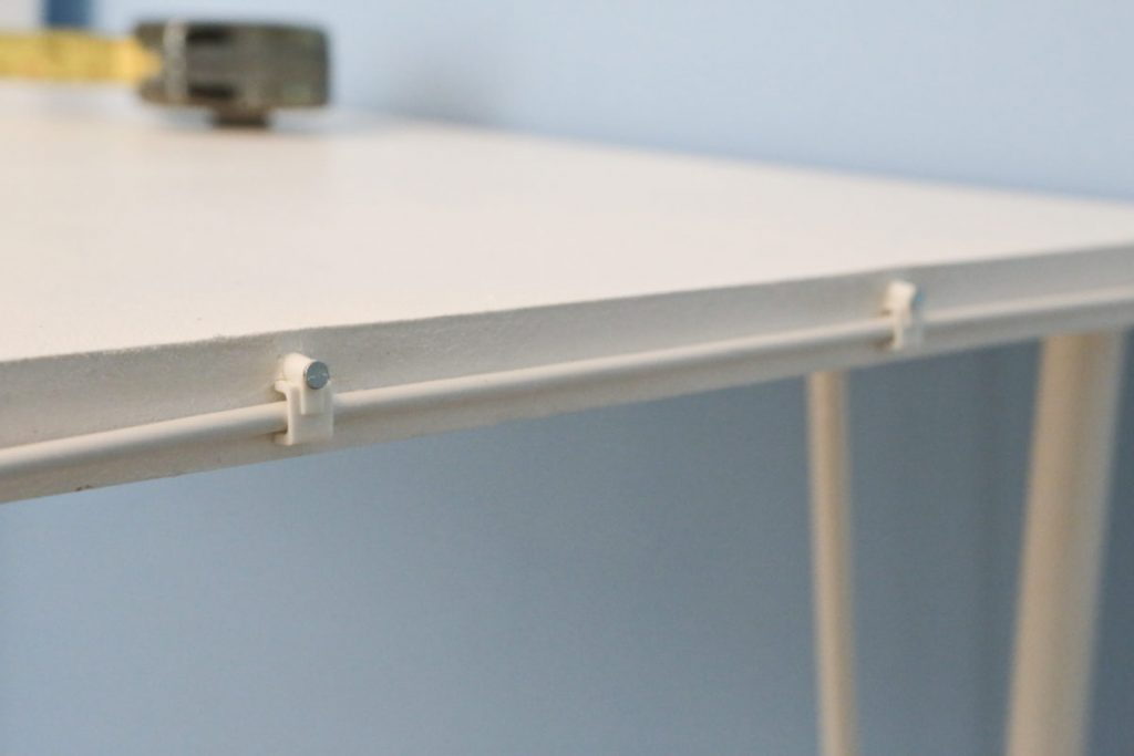 Close-up of net curtain wire attached to side edge of desk and held in place with cable tacks.