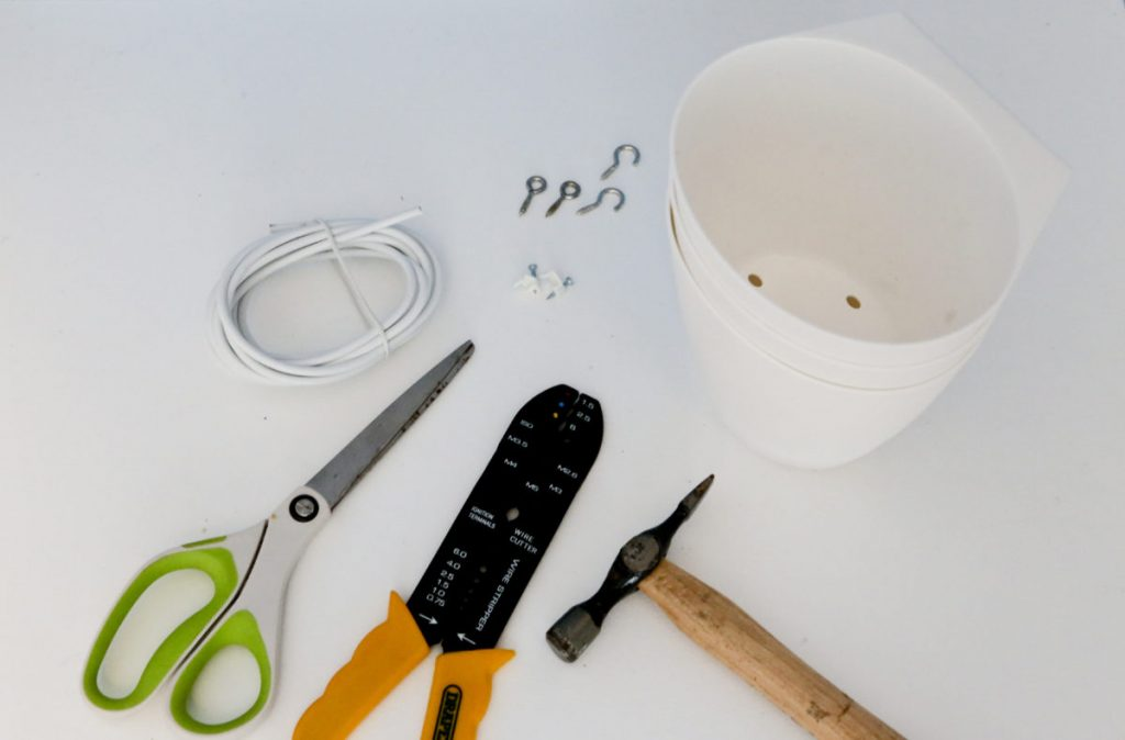 Materials and equipment needed to make a Children's Ikea Hack Desk Tidy. Scissors, wire cutters, hammer, hooks and eyes, net curtain wire, Ikea Bygel container, cable tidys.