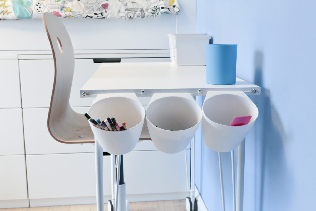 Close-up side view of Children's Ikea Hack Desk Tidy. Desk and chair in front of bed with three Bygel containers hanging on a net curtain wire on the end of a children's white desk
