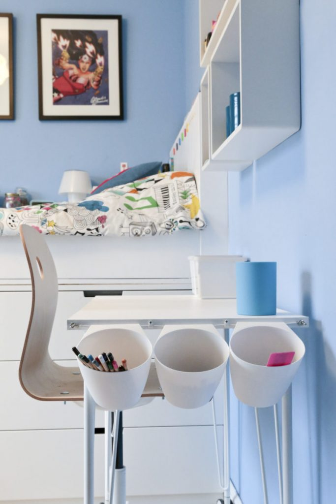 Side view of Children's Ikea Hack Desk Tidy. Desk and chair in front of bed with three Bygel containers hanging on a net curtain wire on the end of a children's white desk