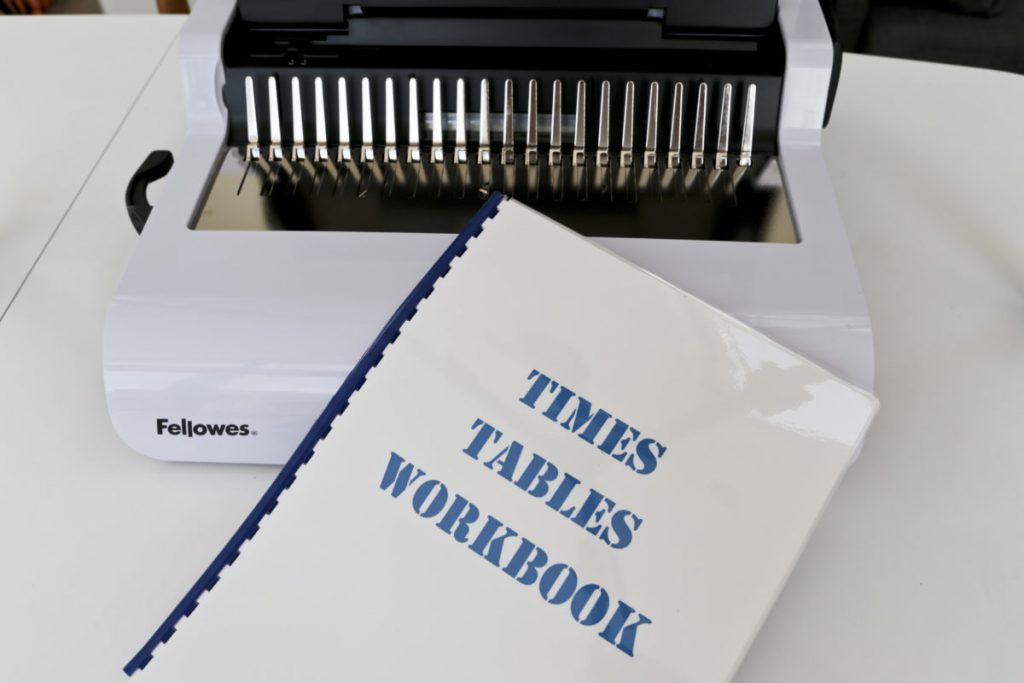 The completed bound times table workbook in front of the Fellowes Pulsar 300 Comb Binder Lid Closed
