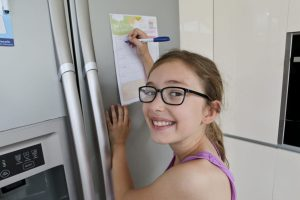 Emily facing camera and Writing on the laminated TO DO list on the fridge