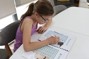 Emily working through her times table answers in her workbook using a dry wipe marker