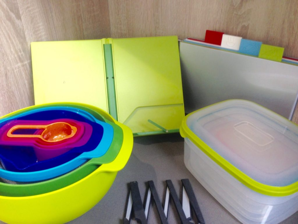 My collection of Joseph Joseph items including set of mixing bowls, plastic containers, pan trivet, recipe book stand, chopping boards