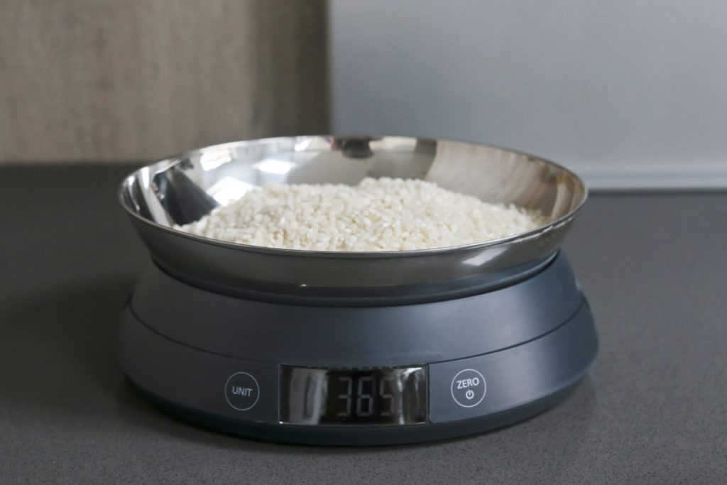 Joseph Joseph SwitchScale 2-in-1 Digital Scale with bowl facing upwards with uncooked rice in bowl with chopping board in the background