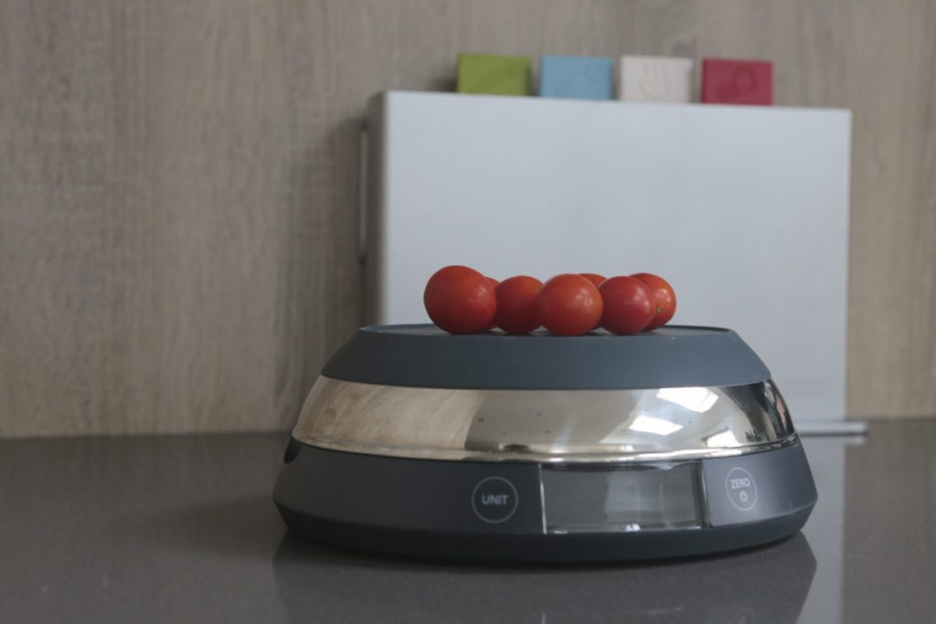 Joseph Joseph SwitchScale 2-in-1 Digital Scale with bowl facing downwards and cherry tomatoes being weighed on top